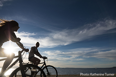 Two people riding bikes on Alki Beach in West Seattle.
