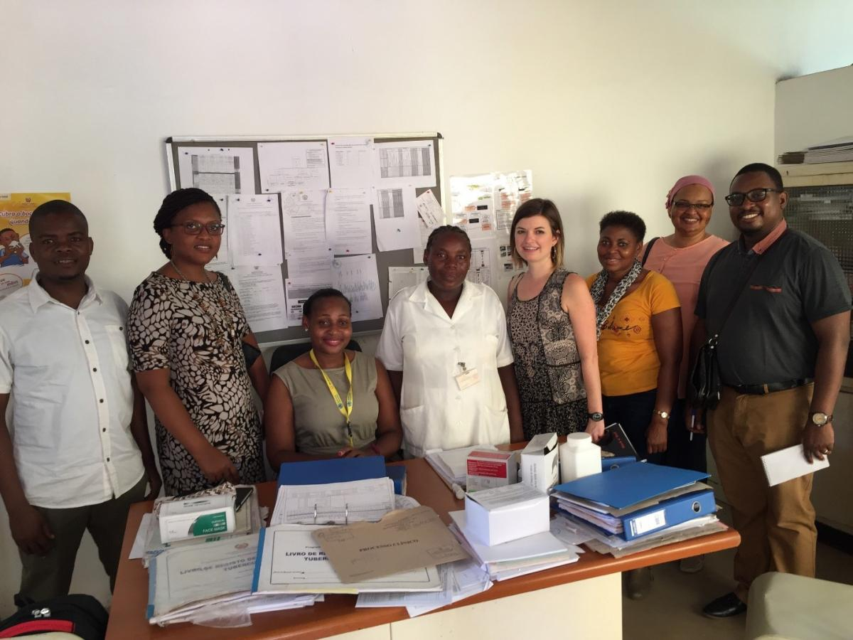 Curran with a TB nurse, TB district supervisor, and CDC and national TB program colleagues at a health facility in Mozambique.