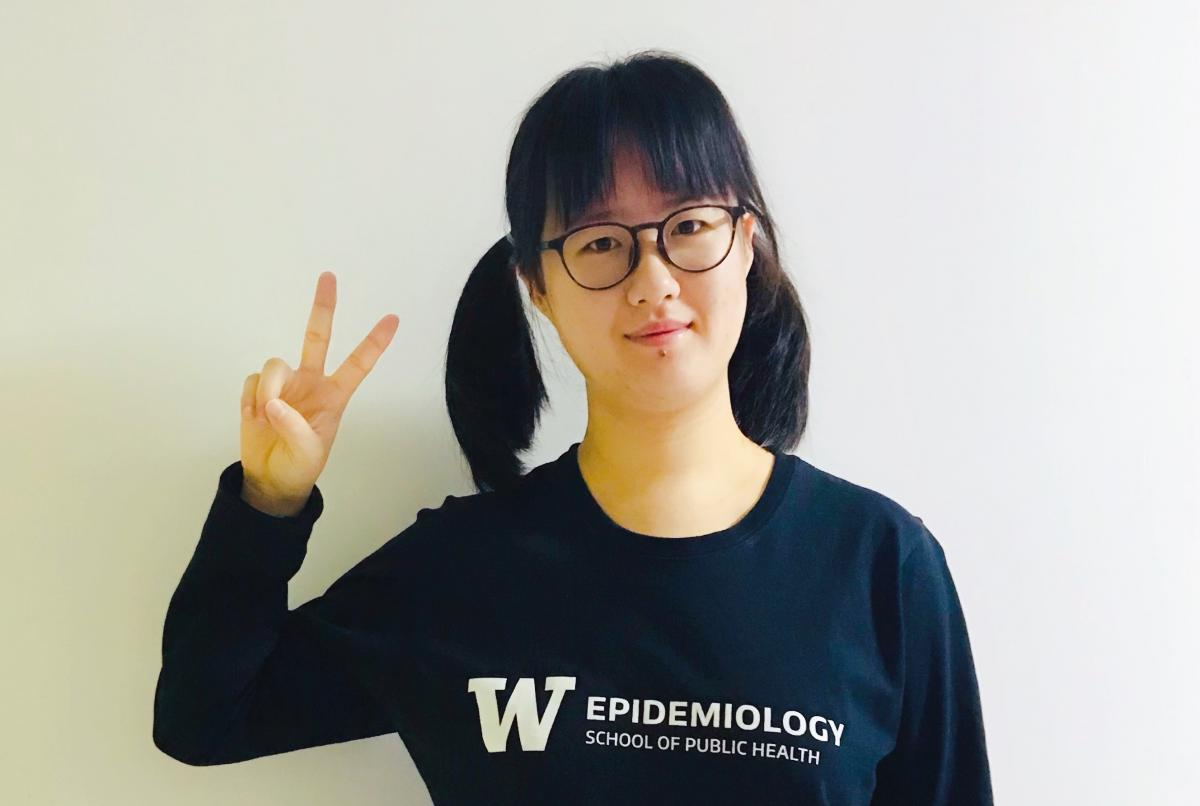 Shengruo is wearing a UW Epidemiology shirt and holds up peace sign.