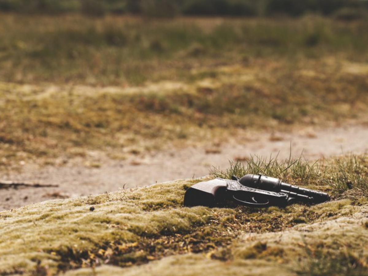 A hand gun laying on the ground.