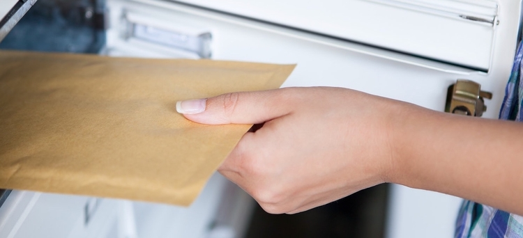 Close-up of hand pulling envelope from mailbox