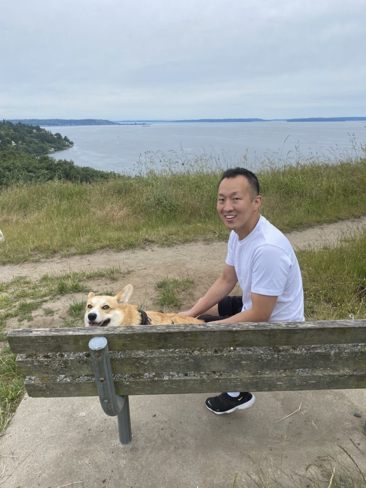 Phillip Hwang on a bench with a dog.