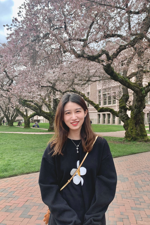 Yuyang Ma stands in front of cherry blossoms on UW campus