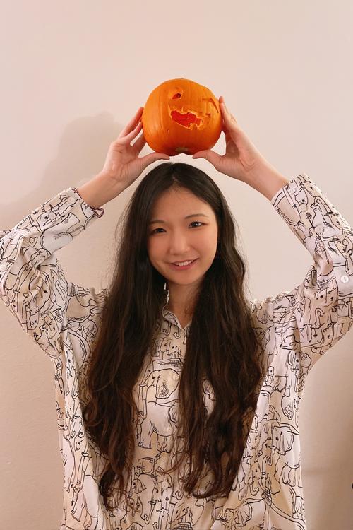 Portrait of Zhuchen Li holding a jack-o'-lantern over her head